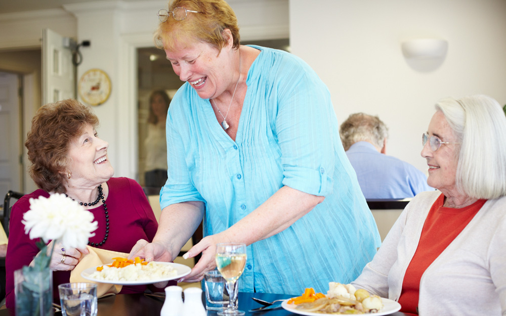 A carer serves two residents lunch