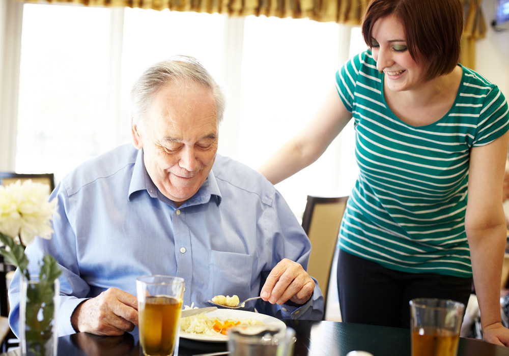 Resident and carer in dining room
